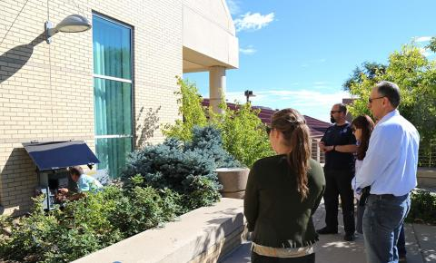 several people observe man installing solar panel at Colorado School of Mines Geology museum