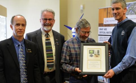 four men with plaque at opening of CMI museum exhibit
