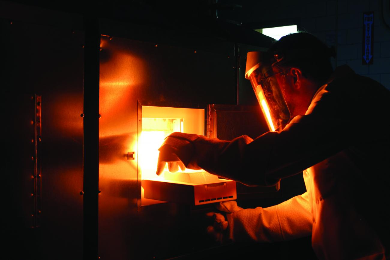 Ames Laboratory scientist Paul Canfield removes a sample from a flux-growth furnace.