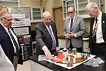 Tom Lograsso, interim CMI Director, shows samples to US Representatives visiting Ames Laboratory